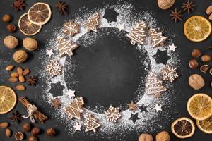 vista superior grinalda de biscoitos de gengibre com frutas cítricas e nozes secas foto