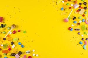 vários pirulitos coloridos na superfície amarela foto
