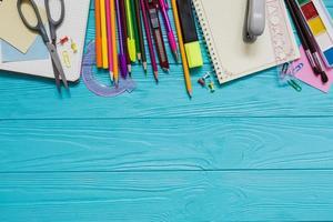 variedade de materiais escolares na mesa de madeira azul foto