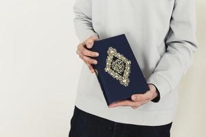 conceito de ramadã com homem segurando Alcorão foto