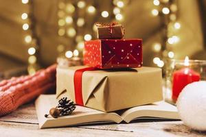 caixas de presentes e livro perto de vela acesa foto