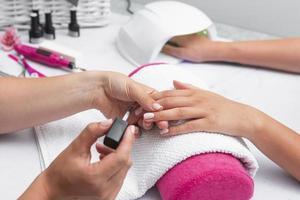 vista lateral mulher fazendo manicure para cliente foto