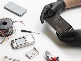 homem segurando telefone com tela quebrada foto