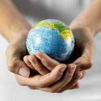 pessoa segurando um globo terrestre foto