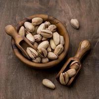 pistache torrado em tigelas de madeira foto