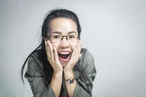 mulher surpresa usando óculos em fundo cinza foto