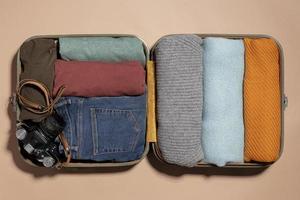 bagagem aberta com roupa dobrada e câmera foto