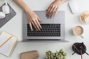 desktop vista de cima com laptop e mãos foto