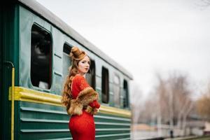 jovem com cabelo ruivo em um vestido vermelho brilhante perto de um velho carro de passageiros foto