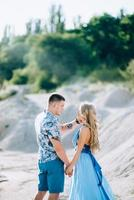 garota loira com um vestido azul claro e um cara com uma camisa leve em uma pedreira de granito foto