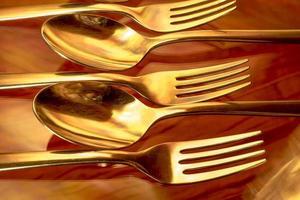 talheres de ouro em uma mesa foto