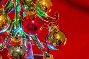 enfeites de uma mini árvore de natal feita de vidro iluminado foto