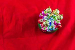 mini árvore de natal de vidro iluminada em fundo vermelho foto