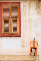 cadeira laranja pendurada na parede e bela janela de madeira de uma casa tradicional na cidade velha de nicosia, chipre foto