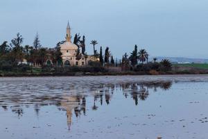 hala sultan tekke e reflexão sobre o lago salgado de larnaca, chipre foto