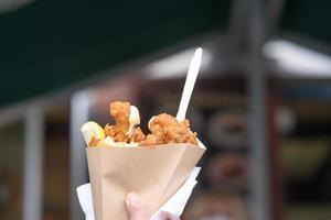 mão masculina segurando peixe britânico com batatas fritas em um cone de papel foto