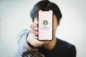 chiang mai, tailândia, 23 de janeiro de 2021 - pessoa segurando um telefone com o aplicativo starbucks nele foto