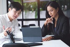 dois profissionais em uma reunião com um tablet foto