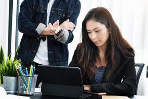 mulher trabalhando em um tablet com um homem falando atrás dela foto
