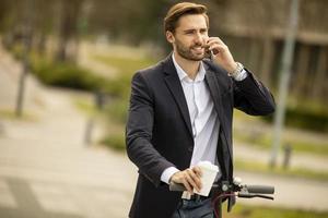 jovem empresário usando telefone celular em scooter elétrico foto