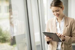jovem segurando um tablet digital em um escritório moderno foto