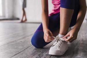 menina de seção baixa amarrando sapatos brancos de cadarço. conceito de foto bonita de alta qualidade e resolução
