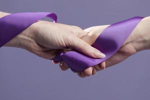 mãos de mulheres segurando uma fita de cetim roxa. conceito de foto bonita de alta qualidade e resolução