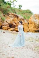 noiva em um vestido azul claro caminhando à beira-mar foto