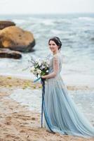 noiva com um buquê de flores na praia foto