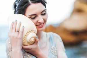 noiva com uma grande concha na praia foto