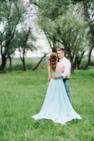 cara feliz em uma camisa branca e uma garota em um vestido turquesa estão caminhando no parque florestal foto