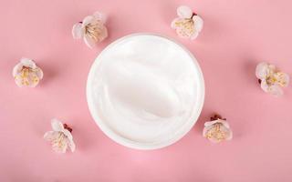 creme e flores em fundo rosa, cosmético de beleza para cuidados com a pele foto
