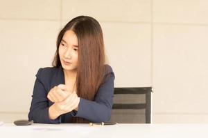 mulher de negócios asiáticos segurando a dor no pulso de trabalhar e usar o computador. síndrome de escritório foto