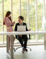 jovem empresário asiático e empresária trabalhando em um ambiente de escritório com fundo natural foto