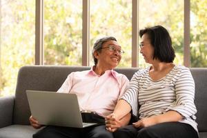 mulher e homem asiático sênior relaxam nas férias no fundo natural da sala de estar com tecnologia moderna foto