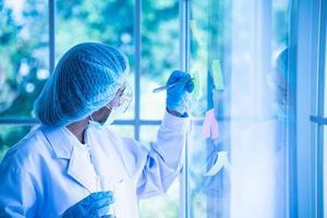 mulheres jovens asiáticas cientista testando e analisando produtos químicos no laboratório foto