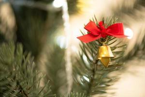 árvore de natal decorada na sala de estar para se preparar para o ano novo. decore a sala de estar e a árvore de natal com uma caixa de bolas vermelhas, bolas douradas, sinos dourados, estrelas de neve, meias. foto