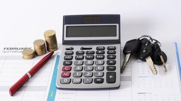 calculadora e pilha de moedas e caneta de negócios e chave do carro no calendário para o conceito de empréstimo foto