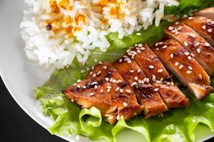comida caseira frango teriyaki com arroz branco e pimenta em um fundo preto foto