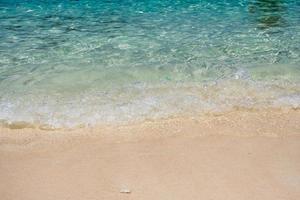 mar de ondas cristalinas com praia de areia foto