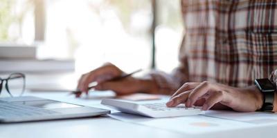 close-up do homem ou mão do contador segurando a caneta trabalhando na calculadora para calcular o relatório de dados financeiros, documento contábil e laptop no escritório. foto