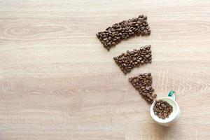 muitos grãos de café torrados em uma xícara de cerâmica e moldados em um sinal de internet wi-fi foto