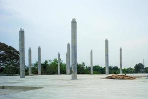 perspectiva de colunas de concreto no chão de cimento no canteiro de obras com fundo de céu claro foto