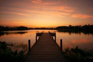 passarela de madeira no lago com cenário natural do pôr do sol e a silhueta da floresta no fundo foto
