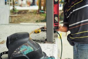 trabalhador mede o nível perpendicular durante a instalação do poste de aço no canteiro de obras pela régua de nivelamento foto