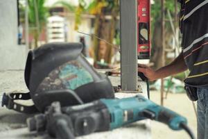 trabalhador mede o nível perpendicular durante a instalação do poste de aço no canteiro de obras pela régua de nivelamento com ferramentas borradas em primeiro plano foto