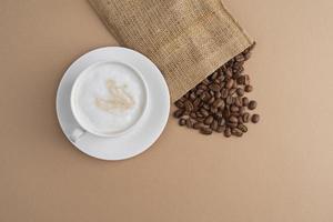 saco de pano com xícara de grãos de café foto