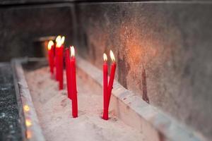 grupo de velas vermelhas colocadas na areia em uma bandeja de concreto foto