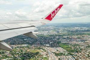 Banguecoque, Tailândia - 8 de junho de 2020 - asa close-up de um avião da Air Asia enquanto voava no ar com a paisagem urbana abaixo foto