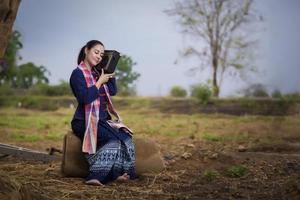 mulher tailandesa no campo de arroz e na casa de campo, atividade de estilo de vida do agricultor conceito foto